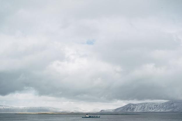 Barka pływa po oceanie atlantyckim w pobliżu islandii na tle ośnieżonych gór