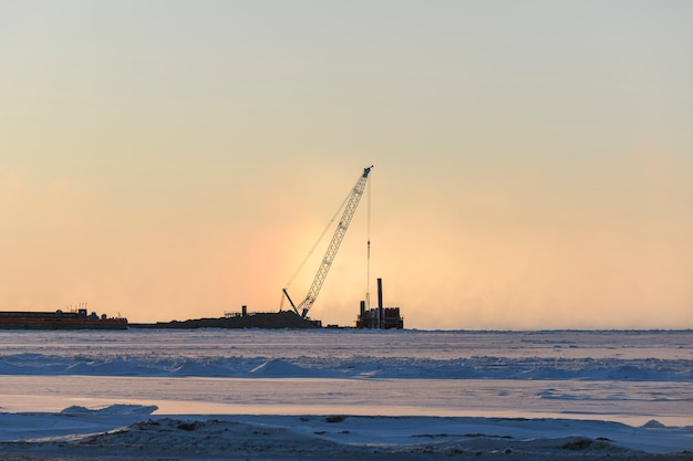 Barka z dźwigiem. pogłębiarka pracująca na morzu. zachód słońca na morzu arktycznym. roboty budowlane na morzu. budowa zapory, dźwig, barka, pogłębiarka.
