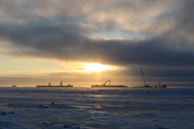 Barka z dźwigiem. pogłębiarka pracująca na morzu. zachód słońca na morzu arktycznym. roboty budowlane na morzu.