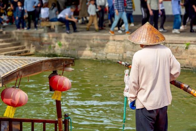 Barkarz z paddle blisko tradycyjnej turystycznej łodzi na kanale szanghaj zhujiajiao stary miasteczko w szanghaj, chiny.