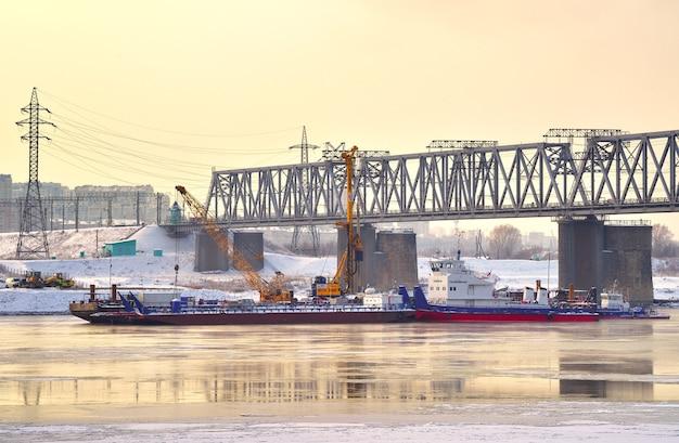 Barki pod mostem kolejowym budowa centralnych filarów mostu zimą