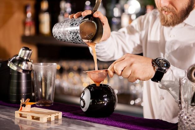 Barman barman nalewa drinka. napój alkoholowy