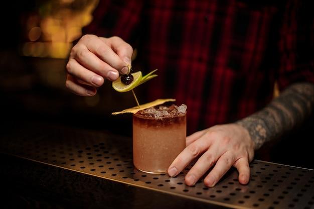 Barman dekorujący na blacie świeży słodki i smaczny koktajl tropic plasterkami owoców