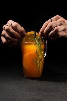 Barman dekoruje gorący napój herbaciany z rokitnikiem i cytrusami plasterkiem pomarańczy w przezroczystym szklanym kubku.