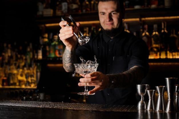 Barman dorzucający do napoju alkoholowego w szklance dużą kostkę lodu za pomocą pęsety na blacie barowym