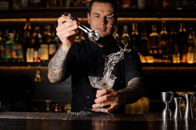 Barman dorzucający do napoju alkoholowego w szklance kostkę lodu za pomocą pęsety z pluskiem na blacie barowym