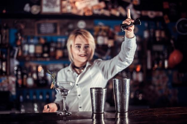 Barman dziewczyna miesza koktajl w piwiarni