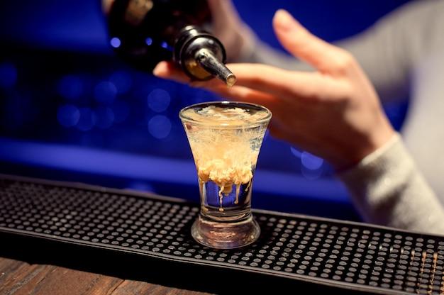 Barman dziewczyna przygotowuje alkoholowego guza mózgu.