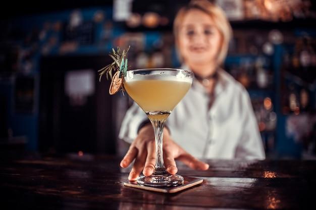 Barman dziewczyna przygotowuje koktajl w piwiarni