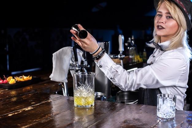 Barman dziewczyna robi koktajl w pothouse