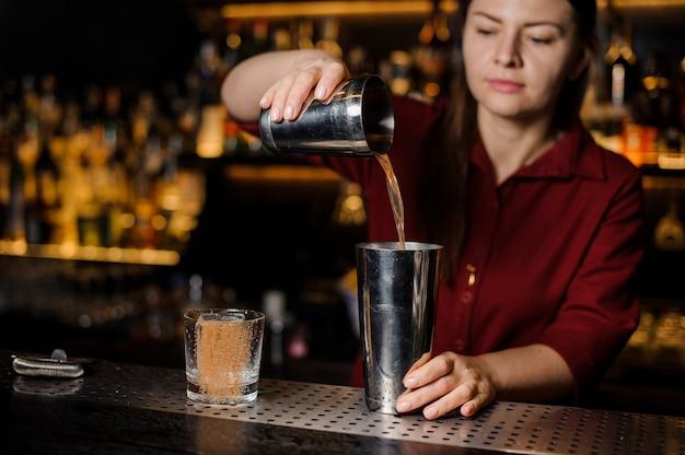 Barman dziewczyna robi koktajlowi przy barowym kontuarem