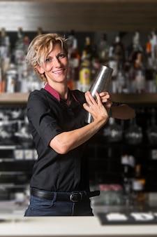 Barman kobieta patrzeje napój i przygotowywa.