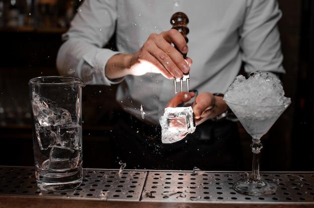 Barman łamie kostkę lodu na koktajl za pomocą specjalnego narzędzia