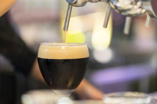Barman leje czarne piwo w szklance.