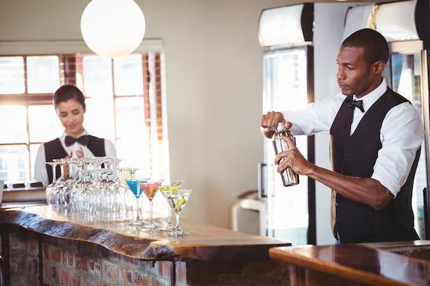 Barman mieszający napój koktajlowy w shakerze
