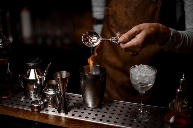 Barman nalewa esencję z łyżki do stalowego shakera z ogniem