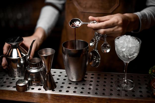 Barman nalewa esencję z łyżki do stalowej wytrząsarki