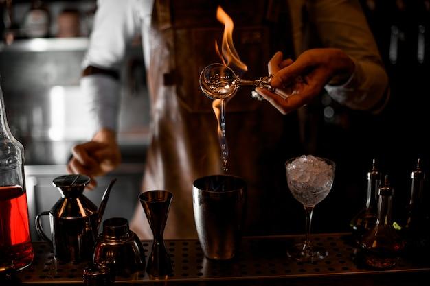 Barman nalewa esencję z łyżki w płomieniu do stalowej wytrząsarki