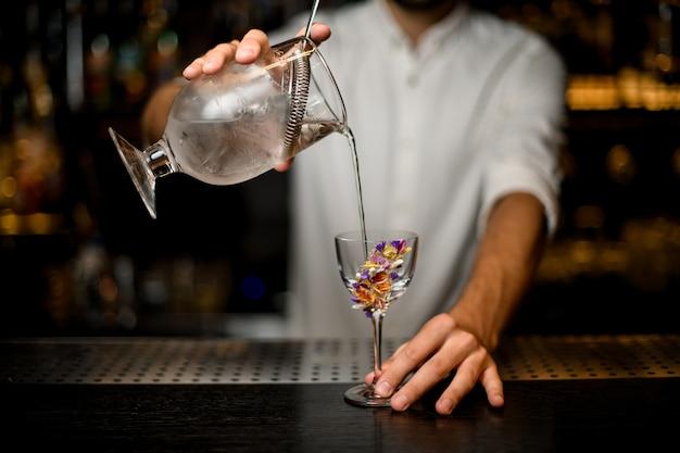 Barman nalewa koktajl z miarki z sitkiem do szklanki zdobionej kwiatem
