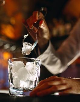 Barman nalewa lód do kieliszków koktajlowych