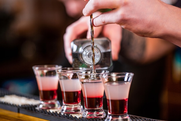 Barman nalewa mocny trunek do małych szklanek na barze.