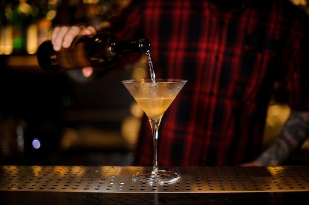 Barman nalewa napój do eleganckiego kieliszka koktajlowego
