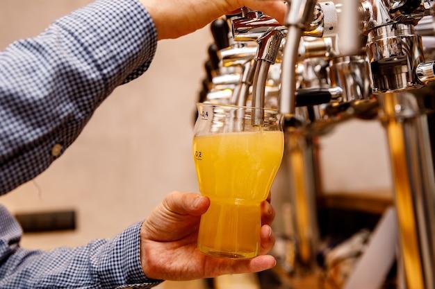 Barman nalewa świeże, jasne piwo z kranu w pubie