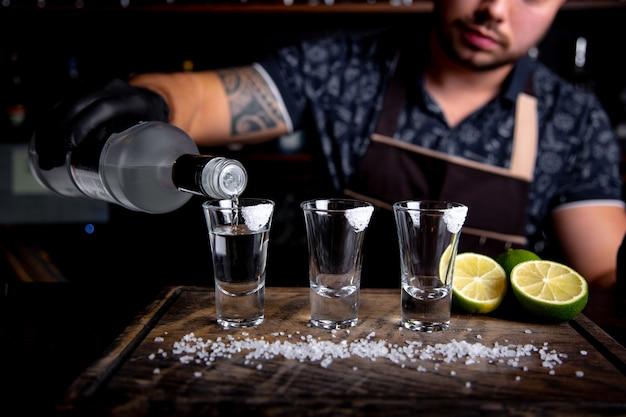 Barman nalewa twardego ducha do małych szklanek