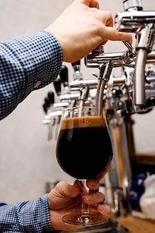 Barman nalewa w pubie świeże, ciemne piwo z kranu