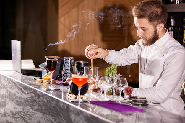 Barman nalewający dodatki do koktajli. lounge atmosfera