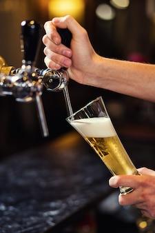 Barman nalewający świeże piwo do pubu, ręka barmana przy nalewaniu piwa nalewającego piwo lagerowe, piwo z beczki, napełnianie szklanki piwem, pub.bar.restauracja.europejski bar.amerykański bar.