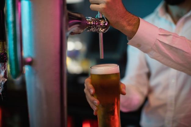 Barman napełniający piwo z pompy barowej