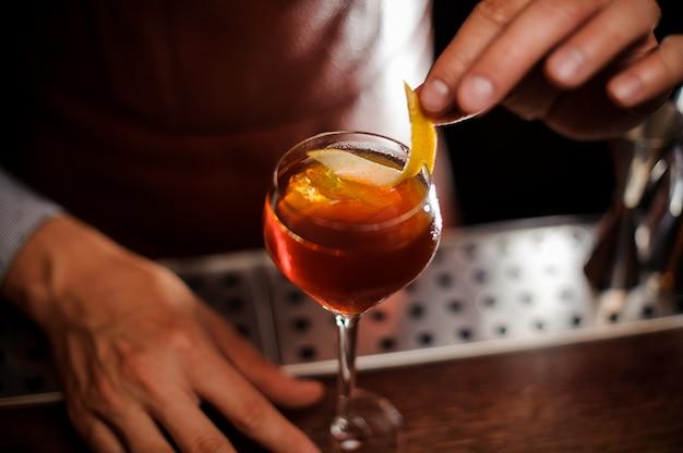 Barman ozdabia koktajl skórką z cytryny