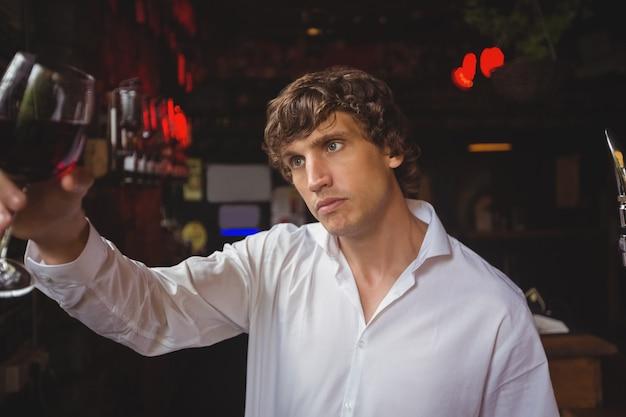 Barman patrzeje szkło czerwone wino