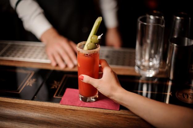 Barman podający kobiecie zakrwawiony koktajl mary z oliwkami i selerem