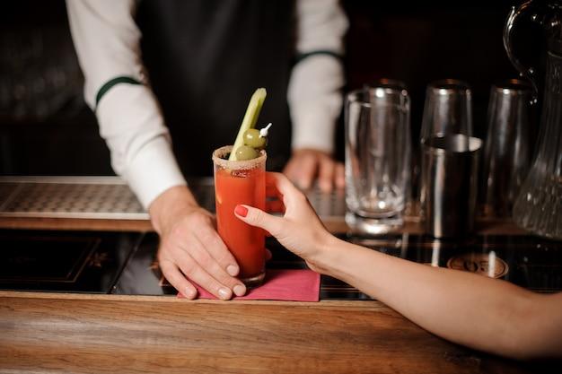 Barman podaje dziewczynie zakrwawiony koktajl mary z oliwkami i selerem