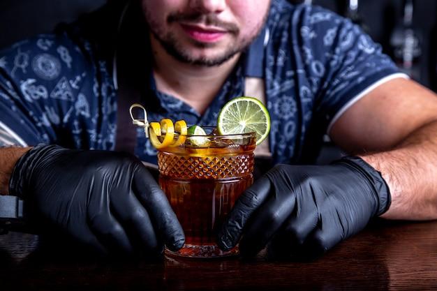 Barman podaje klientowi koktajle w barze w restauracji. witamy