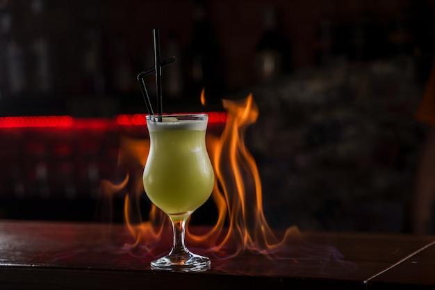 Barman posypuje podświetlone szkło jasnozielonym zimnym koktajlem na ladzie barowej i rozpala nad nią ogień.