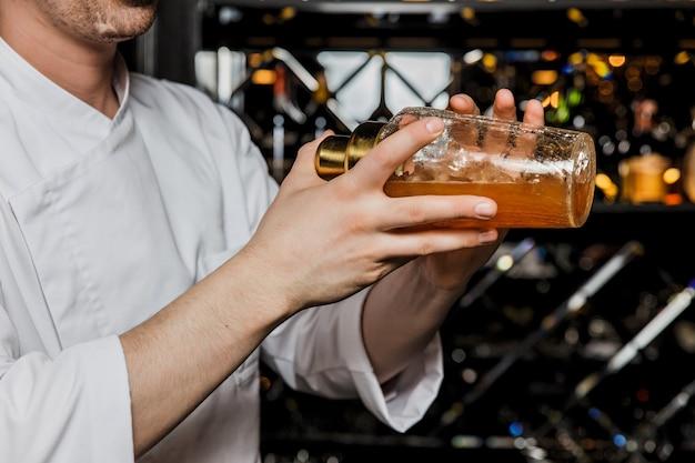 Barman potrząsając koktajlem w szklance