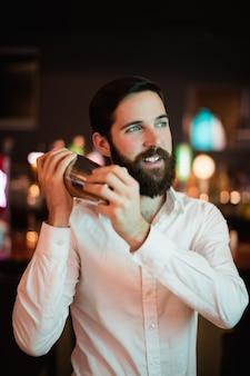 Barman potrząsając shakerem przy barze