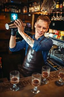 Barman pracuje z shakerem przy blacie barowym