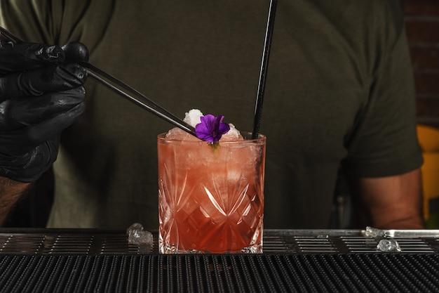 Barman przy barze przyrządzający koktajl alkoholowy z lodem i kwiatem.