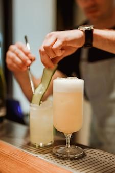 Barman przygotowujący gin z tonikiem z ogórkiem w tle, koktajl pina colada na pierwszym planie. zdjęcie z małą głębią ostrości. obraz w pionie stylu życia.