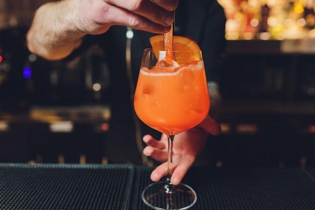 Barman przygotowuje alkoholowy aperitif, aperolowy koktajl spritz.