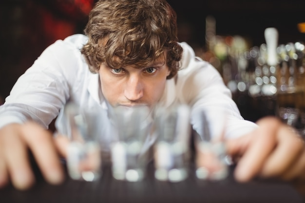 Barman przygotowuje i wykłada szklanki do napojów alkoholowych na blacie barowym