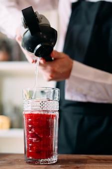 Barman przygotowuje koktajl jagodowy na tarasie restauracji.