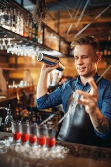 Barman przygotowuje koktajl, stojąc w lodzie szklanki