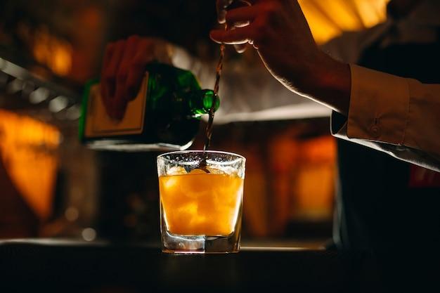 Barman przygotowuje koktajl w barze barman nalewa alkohol z butelki