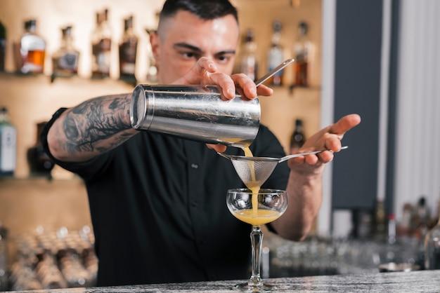 Barman przygotowuje orzeźwiający koktajl
