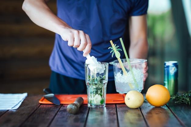 Barman przygotowuje owocowy koktajl alkoholowy na bazie limonki, mięty, pomarańczy, sody i alkoholu